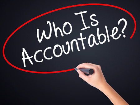 accountable: Woman Hand Writing Who Is Accountable? on blank transparent board with a marker isolated over black background. Business concept. Stock Photo
