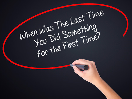 promptness: Woman Hand Writing When Was The Last Time You Did Something for the First Time? on blank transparent board with a marker isolated over black background. Business concept. Stock Photo Stock Photo