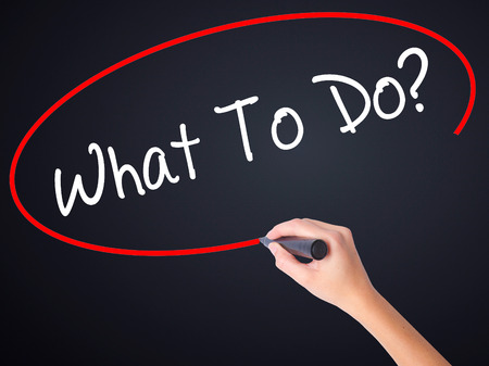 Woman Hand Writing  What To Do? on blank transparent board with a marker isolated over black background. Stock Photo