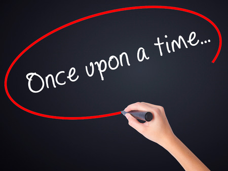phrase novel: Woman Hand Writing Once upon a time... on blank transparent board with a marker isolated over black background. Business concept. Stock Photo