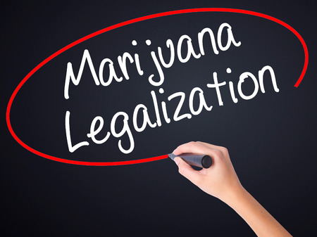 legislators: Woman Hand Writing Marijuana Legalization with a marker over transparent board . Isolated on white. Live, technology, internet concept. Stock Photo Stock Photo