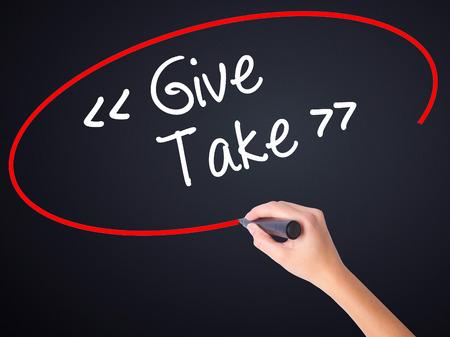 generosa: Mujer escritura de la mano Dar - Tome a bordo transparente blanco con un marcador aislado sobre fondo negro. Foto de stock Foto de archivo