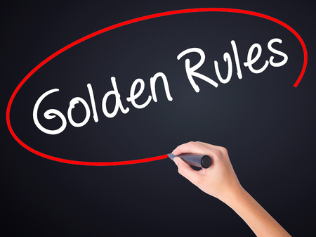golden rule: Woman Hand Writing Golden Rules on blank transparent board with a marker isolated over black background. Business concept. Stock Photo
