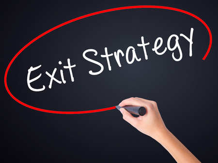 downsize: Woman Hand Writing Exit Strategy on blank transparent board with a marker isolated over black background. Stock Photo