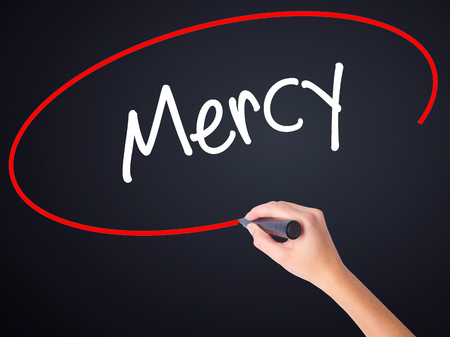 mercy: Woman Hand Writing Mercy on blank transparent board with a marker isolated over black background. Business concept. Stock Photo