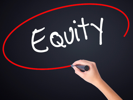 equity: Woman Hand Writing Equity on blank transparent board with a marker isolated over black background. Stock Photo