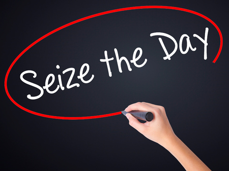 seize: Woman Hand Writing Seize the Day on blank transparent board with a marker isolated over black background. Stock Photo