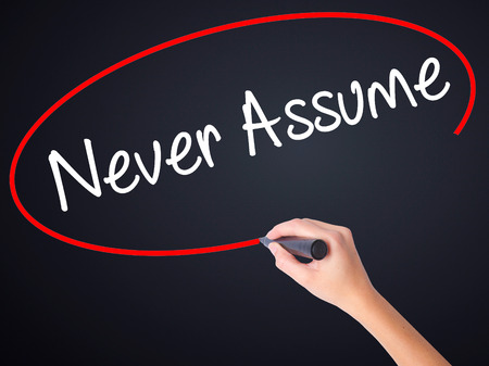 assume: Woman Hand Writing Never Assume on blank transparent board with a marker isolated over black background. Stock Photo Stock Photo
