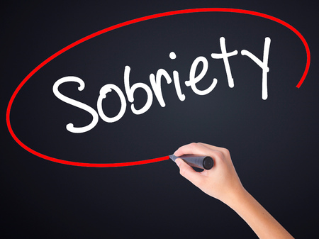 sobriety: Woman Hand Writing Sobriety on blank transparent board with a marker isolated over black background. Business concept. Stock Photo