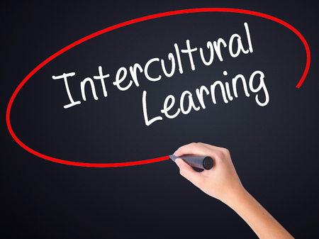 intercultural: Woman Hand Writing Intercultural Learning on blank transparent board with a marker isolated over black background. Business concept. Stock Photo