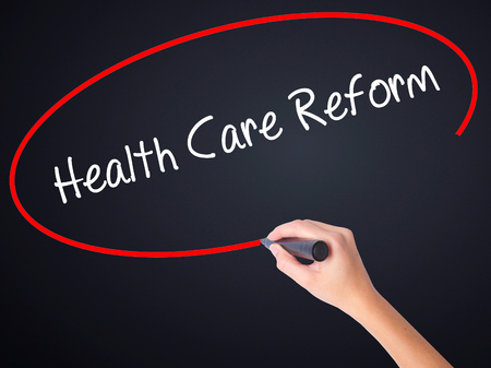hmo: Woman Hand Writing Health Care Reform on blank transparent board with a marker isolated over black background. Business concept. Stock Photo