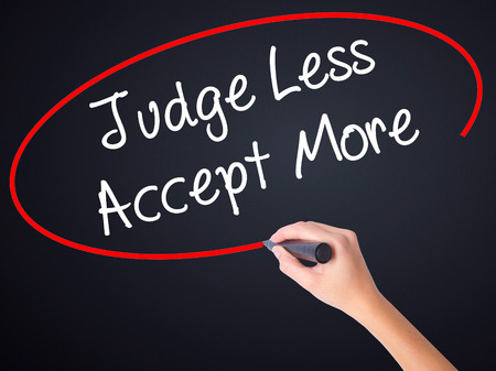 and is favorable: Woman Hand Writing Judge Less Accept More on blank transparent board with a marker isolated over black background. Stock Photo