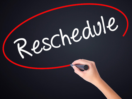 rescheduling: Woman Hand Writing Reschedule  on blank transparent board with a marker isolated over black background. Stock Photo