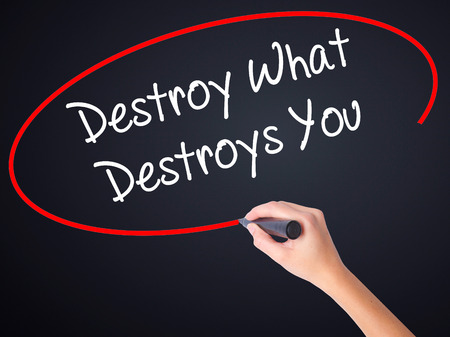 annihilate: Woman Hand Writing Destroy What Destroys You on blank transparent board with a marker isolated over black background. Stock Photo