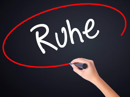 Woman Hand Writing Ruhe (Quiet in German) on blank transparent board with a marker isolated over black background. Stock Photo