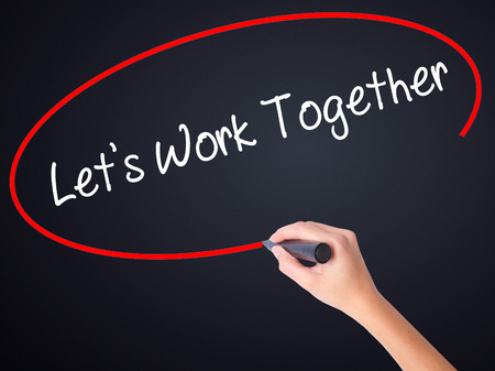 harmonize: Woman Hand Writing Lets Work Together on blank transparent board with a marker isolated over black background. Stock Photo