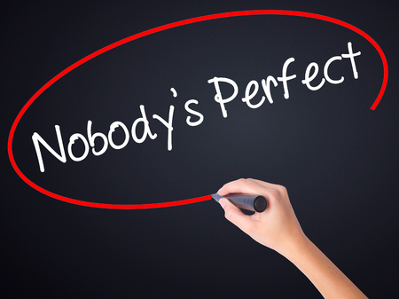 perfectionist: Woman Hand Writing Nobodys Perfect on blank transparent board with a marker isolated over black background. Stock Photo