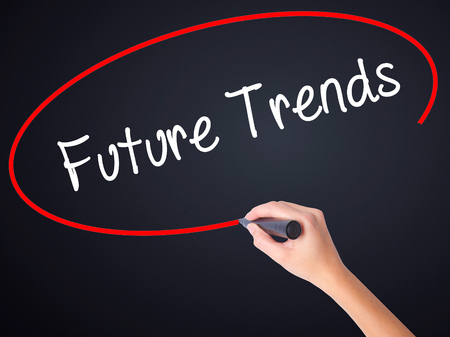 adwords: Woman Hand Writing Future Trends on blank transparent board with a marker isolated over black background. Business concept. Stock Photo Stock Photo