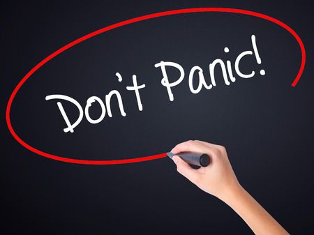 Woman Hand Writing Dont Panic! on blank transparent board with a marker isolated over black background. Stock Photo