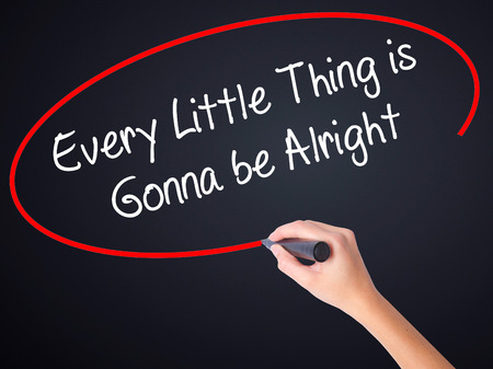 alright: Woman Hand Writing Every Little Thing is Gonna be Alright on blank transparent board with a marker isolated over black background. Business concept. Stock Photo