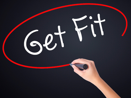 work less: Woman Hand Writing Get Fit  on blank transparent board with a marker isolated over black background. Stock Photo Stock Photo