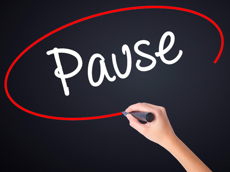 HESITATE: Woman Hand Writing Pause on blank transparent board with a marker isolated over black background. Stock Photo Stock Photo