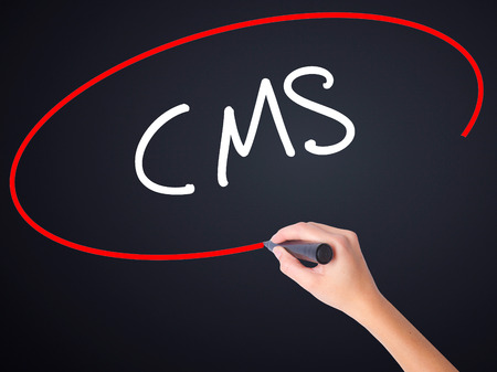 meta data: Woman Hand Writing CMS (Custom Management System) on blank transparent board with a marker isolated over black background. Stock Photo
