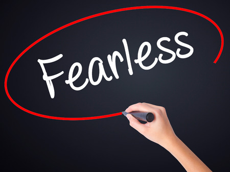 assured: Woman Hand Writing Fearless  on blank transparent board with a marker isolated over black background. Stock Photo