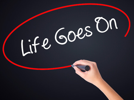 Woman Hand Writing Life Goes On on blank transparent board with a marker isolated over black background. Business concept. Stock Photo