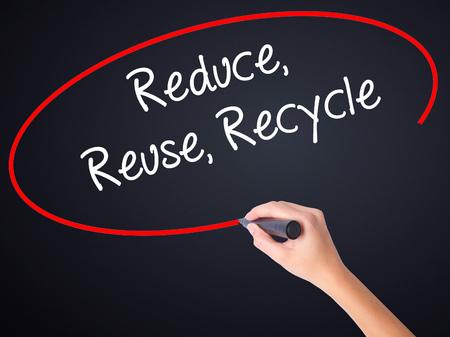 recycle reduce reuse: Escritura de la mano de la mujer reduce la reutilización recicla a bordo transparente blanco con un marcador aislado sobre fondo negro. Foto de stock