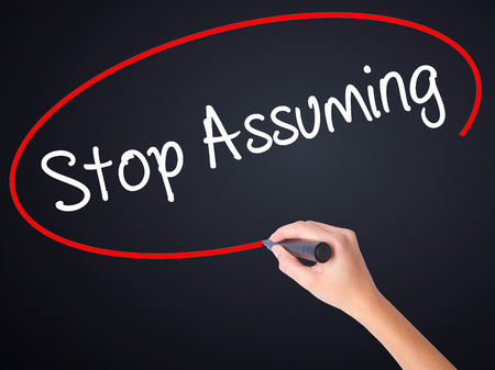 inference: Woman Hand Writing Stop Assuming on blank transparent board with a marker isolated over black background. Stock Photo