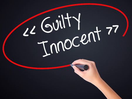 fair trial: Woman Hand Writing Guilty - Innocent on blank transparent board with a marker isolated over black background. Stock Photo