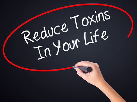 toxins: Woman Hand Writing Reduce Toxins In Your Life on blank transparent board with a marker isolated over black background. Business concept. Stock Photo