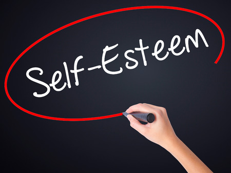self worth: Woman Hand Writing Self-Esteem on blank transparent board with a marker isolated over black background. Stock Photo