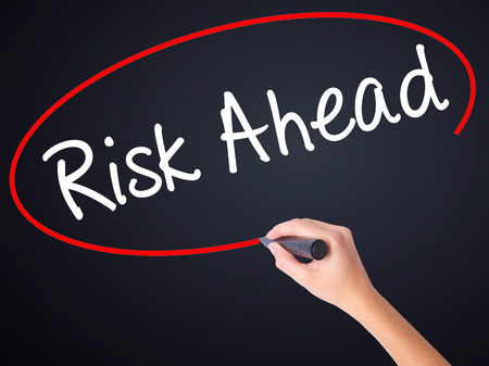 Woman Hand Writing Risk Ahead on blank transparent board with a marker isolated over black background. Business concept. Stock Photo Stock Photo