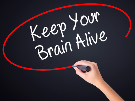 alive: Woman Hand Writing Keep Your Brain Alive on blank transparent board with a marker isolated over black background. Stock Photo Stock Photo