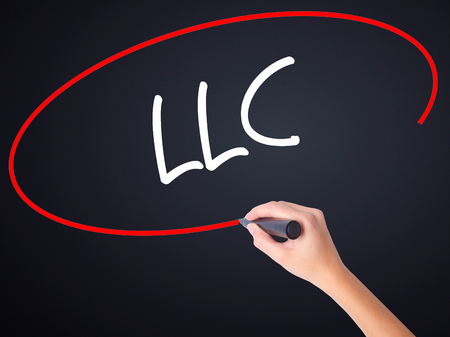 incorporation: Woman Hand Writing  LLC (Limited Liability Company)  on blank transparent board with a marker isolated over black background. Stock Photo