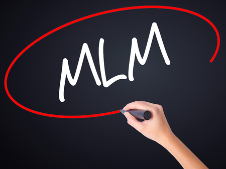 multilevel: Woman Hand Writing  MLM (Multi-Level Marketing) on blank transparent board with a marker isolated over black background. Stock Photo
