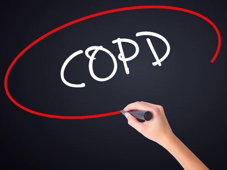 Woman Hand Writing COPD on blank transparent board with a marker isolated over black background. Business concept. Stock Photo