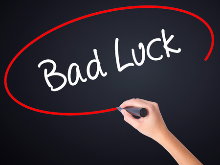 Woman Hand Writing Bad Luck on blank transparent board with a marker isolated over black background. Stock Photo