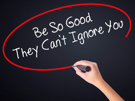 ignore: Woman Hand Writing Be So Good They Cant Ignore You on blank transparent board with a marker isolated over black background. Stock Photo