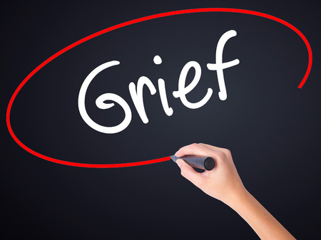 dejection: Woman Hand Writing Grief on blank transparent board with a marker isolated over black background. Stock Photo Stock Photo