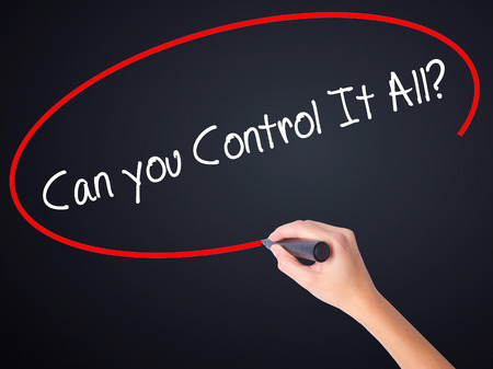 business roles: Woman Hand Writing   Can you Control It All? on blank transparent board with a marker isolated over black background. Business concept. Stock Photo