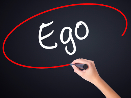 pompous: Woman Hand Writing Ego on blank transparent board with a marker isolated over black background. Stock Photo