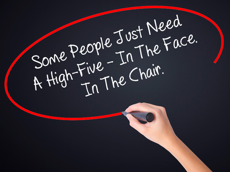 stupidity: Woman Hand Writing Some People Just Need A High-Five - In The Face. In The Chair  on blank transparent board with a marker isolated over black background. Business concept. Stock Photo Stock Photo