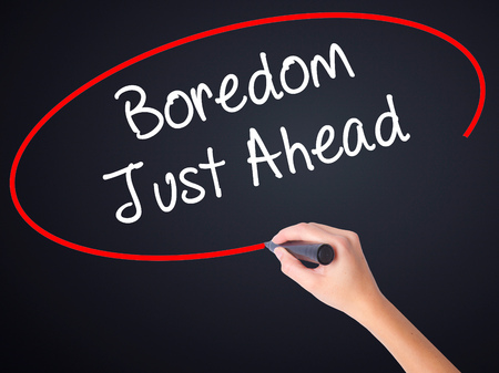 boredom: Woman Hand Writing Boredom Just Ahead on blank transparent board with a marker isolated over black background. Stock Photo Stock Photo