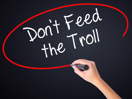 instigator: Woman Hand Writing Dont Feed the Troll on blank transparent board with a marker isolated over black background. Stock Photo