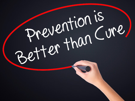 cure prevention: Woman Hand Writing Prevention is Better than Cure on blank transparent board with a marker isolated over black background. Business concept. Stock Photo