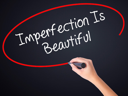 self conceit: Woman Hand Writing Imperfection Is Beautiful on blank transparent board with a marker isolated over black background. Stock Photo