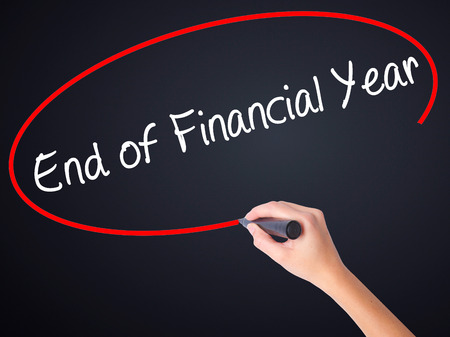Woman Hand Writing End of Financial Year on blank transparent board with a marker isolated over black background. Stock Photo